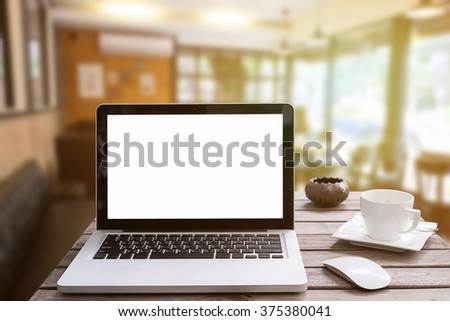 Laptop is on the wood table in a Home office with morning light and vintage tone. - stock photo