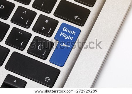 """Laptop key showing the words """"book flight"""", in blue color. - stock photo"""