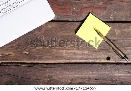 laptop keyboard and sticky notes on rustic wooden table - stock photo