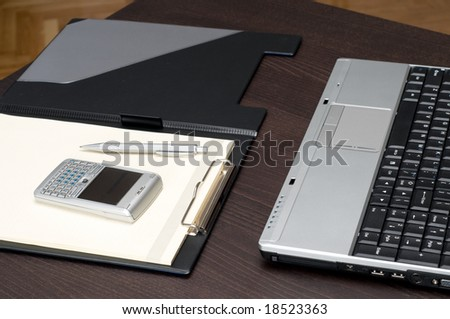 Laptop keyboard,cellphone and empty notepad on office desk