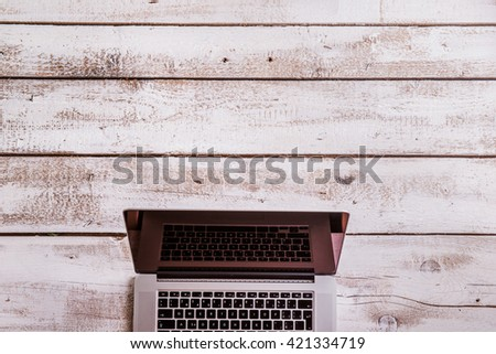 Laptop layid on white wooden office desk. Studio shot. - stock photo