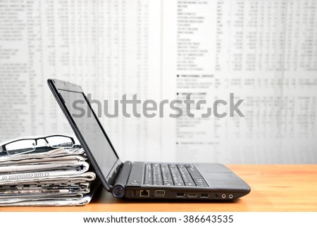 Laptop, newspaper, glasses on wood board with blurred newspaper background - stock photo