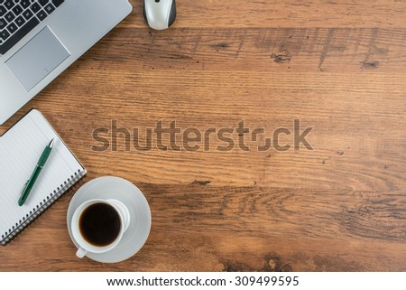 Laptop, notebook and pen with coffee cup on work desk - stock photo