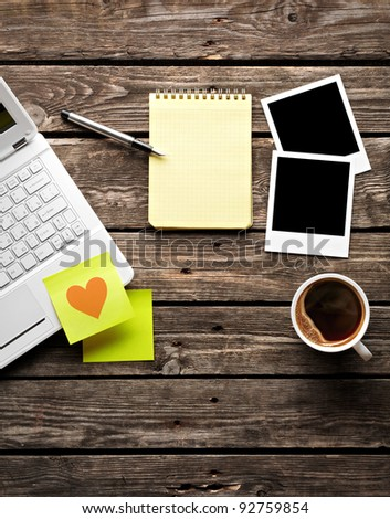 Laptop (notebook) with coffee cup and sticky note paper with notepad on old wooden table. - stock photo