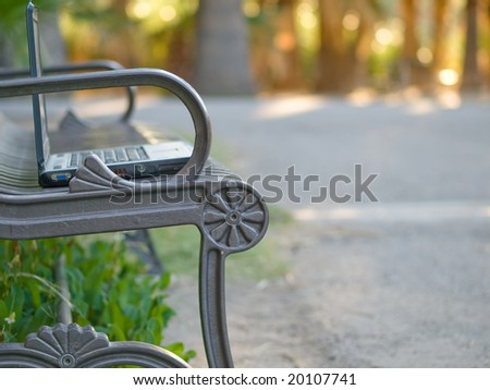 laptop on a bench - stock photo