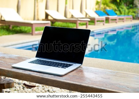 Laptop on a bench by the pool, working on vacation with mobility concept - stock photo