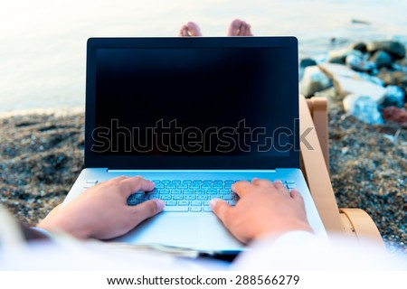 laptop on a man's lap near the sea - stock photo