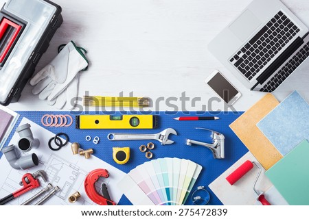 Laptop on a wooden table next to plumbing work tools, tiles, faucet and color swatches top view, online plumbing services concept - stock photo