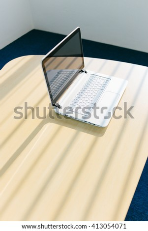 Laptop on desk in silent office with window light