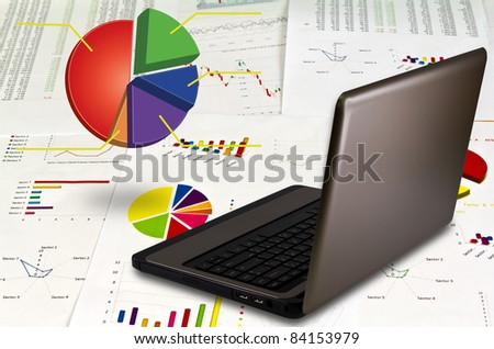 Laptop on financial Graphs - stock photo
