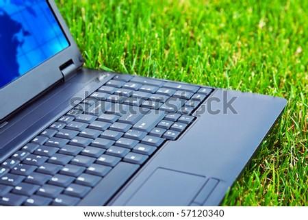 Laptop on grass. Shallow DOF - stock photo