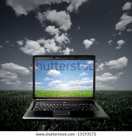 Laptop on green grass on a sunny day - stock photo