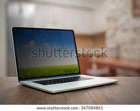 laptop on old wooden table in the kitchen - stock photo