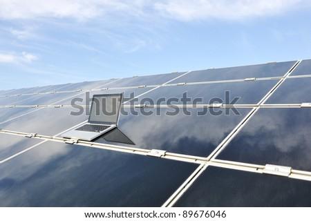 Laptop on  photovoltaic solar panels against blue sky - stock photo