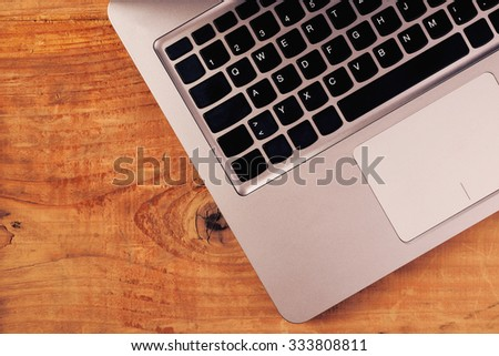Laptop on rustic wooden office desk, retro toned image with blank copy space. Top view of brushed metal computer body with black keyboard in modern freelance business workspace. - stock photo