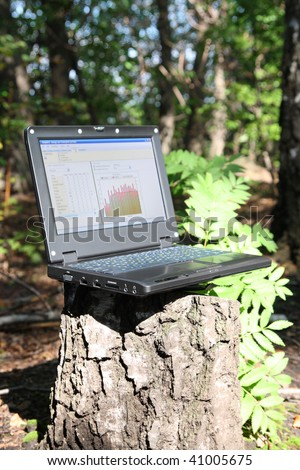 laptop on stump in forest - mobility concept