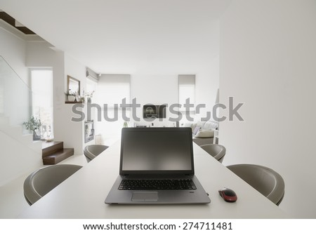 laptop on table in modern dining and living room - stock photo