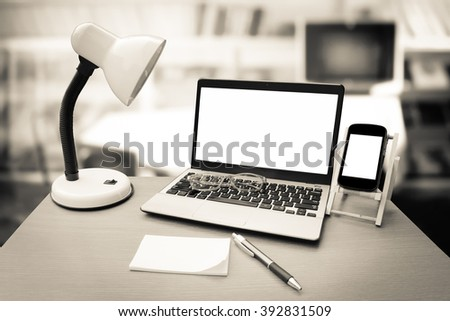 laptop on table with blur library room background