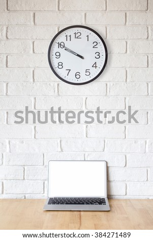 Laptop on table,with white brick wall background,blank screen, clock - stock photo