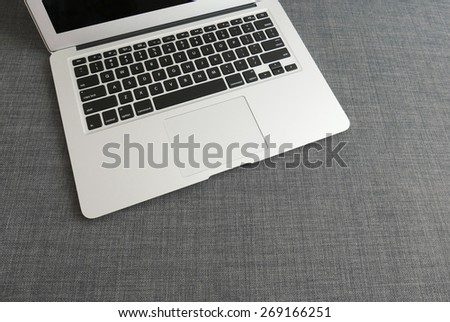 Laptop on the blue cloth background - stock photo
