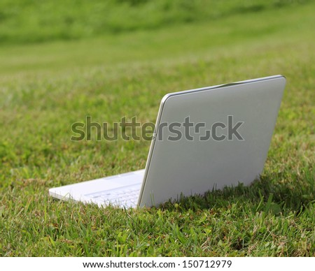 laptop on the green grass - stock photo