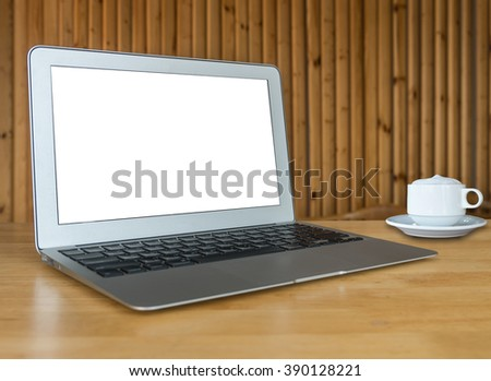 laptop on the wooden table with wooden wall background