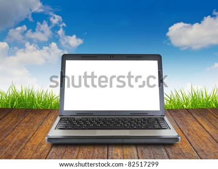 Laptop on wood floor with green grass - stock photo