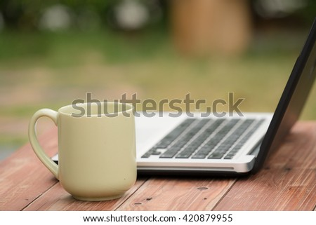 Laptop on wooden table in outdoor with green mug