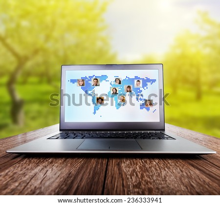 Laptop on wooden table on nature. International communication concept  - stock photo