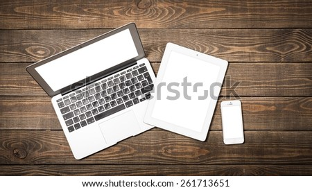 Laptop. Open laptop with digital tablet and white smartphone. All with isolated screen on old wooden desk. - stock photo