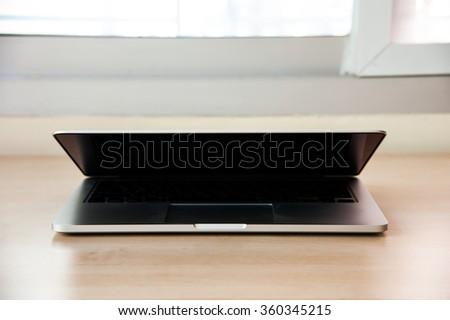 Laptop open on wood table - stock photo