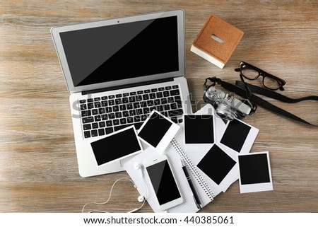 Laptop, phone, photos on a wooden desk background, top view