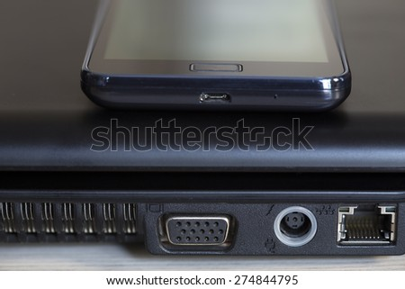 Laptop plug and the mobile phone close up - stock photo