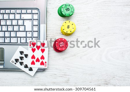 Laptop, poker cards and poker chips - stock photo