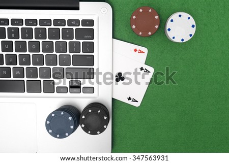 Laptop, poker cards and poker chips, on green background.top view