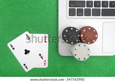 Laptop, poker cards and poker chips, on green background.top view - stock photo