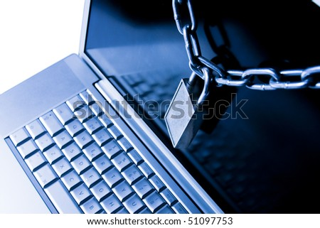 laptop secured with chain and padlock - stock photo