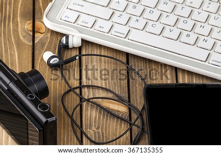 Laptop, smart phone, photo camera and headset on wooden background.