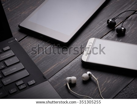 Laptop, smart phone, tablet pc and headset on wooden background - stock photo