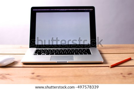 Laptop stands on a wooden table in office