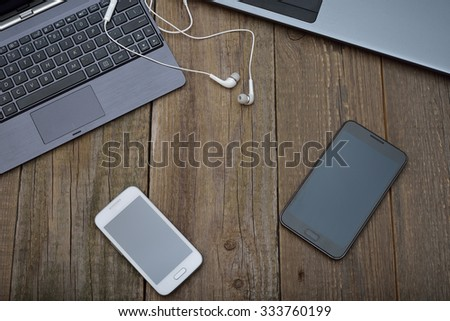 Laptop, tablet and mobile phone on a wooden background - stock photo
