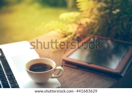 Laptop, tablet, smartphone and a white cup of coffee on wooden background. - stock photo