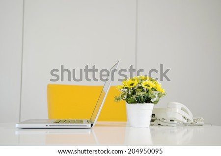 laptop telephone and flower in vase on desk - stock photo
