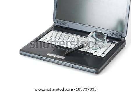 Laptop with a magnify glass isolated on white