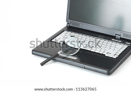 Laptop with a magnify glass on white