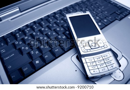 laptop with a mobile phone - stock photo