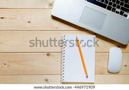 Laptop with blank notepad and pencil with sheets of crumpled paper on old wooden table. Top view  - stock photo