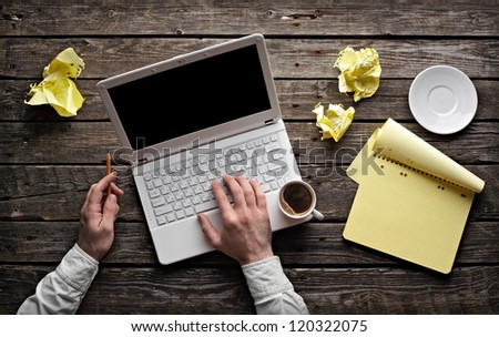 Laptop with blank notepad and pencil with sheets of crumpled paper on old wooden table. Top view of workplace writer. - stock photo
