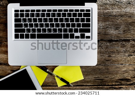 Laptop with blank notepad on old wooden table. - stock photo