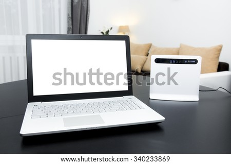 laptop with blank screen and wireless internet router on the table - stock photo